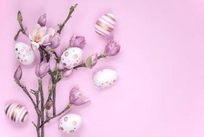 Blooming magnolia branches with Easter-painted eggs on a pink background photo