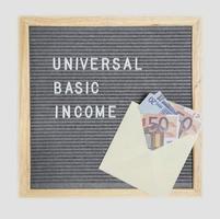 Letterboard con las palabras renta básica universal y un sobre con billetes en euros sobre un fondo blanco. foto