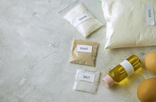 A set of ingredients for baking homemade bread, including wholewheat flour, salt, sugar, sunflower or olive oil, and yeast photo