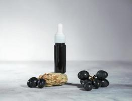 Grapeseed oil in a glass bottle with fresh black grapes, pure essential skincare oil or serum, beauty care natural organic cosmetic concept photo