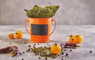 Alga nori crujiente con tomates cherry y especias en un cubo de naranja foto