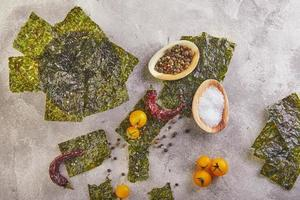 Crujiente de algas nori con tomates cherry y especias sobre hormigón gris