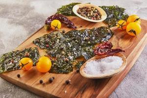 Crujiente de algas nori con tomates cherry y especias sobre una tabla de madera