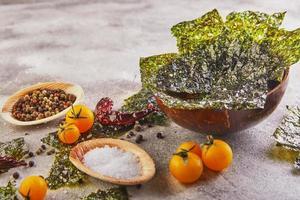 Crujiente de algas nori con tomates cherry y especias en un recipiente de madera sobre hormigón gris