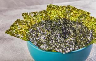 Crujiente de algas nori en un recipiente azul sobre un fondo gris