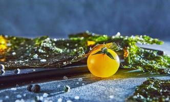 Alga nori crujiente con tomates cherry y especias oscuras sobre hormigón gris foto
