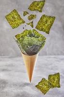 Alga nori crujiente cayendo en una taza cónica sobre un fondo gris, levitación