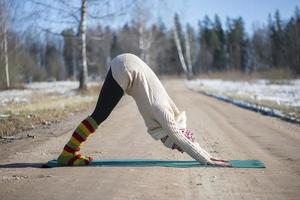 A young athletic woman performs yoga and meditation exercises outdoors