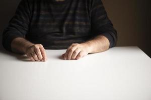 Hombre irreconocible en una posición familiar sentado en una mesa blanca vacía foto