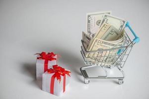 Carrito de compras con dinero y cajas de regalo aisladas foto