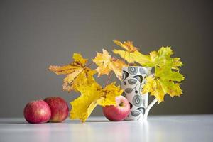 Autumn still life with red apples and colorful maple leaves in a cup on a gray background