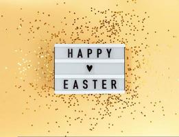 Happy Easter greeting on a lightbox and confetti on a yellow background photo
