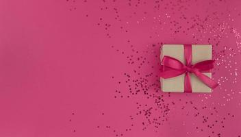 Gift box wrapped in craft paper with a pink ribbon bow and confetti on a pink background, monochrome festive flat lay with copy space