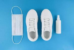 White medical mask, trainers, and hand sanitizer on a blue background, monochrome flat lay quarantine outfit