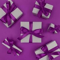 Gift boxes wrapped in craft paper with purple ribbons and bows, festive monochrome flat lay
