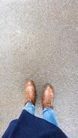 Vista superior selfie de pies de mujer en botas de otoño marrón sobre asfalto mojado después de la lluvia foto