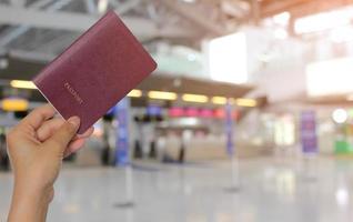 Primer plano de una niña sosteniendo un pasaporte con un fondo de aeropuerto, concepto de viaje