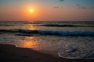 Colorful ocean sea waves during a sunrise or sunset with the sun in the background