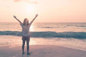 Una mujer levantando sus manos hacia el cielo en una playa durante las vacaciones de verano foto