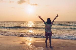 A woman raising her hands up to sky on a beach during summer vacation photo