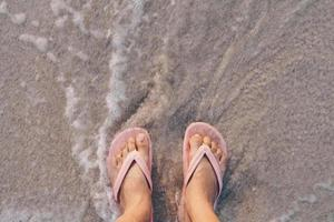 Top view of a woman's feet wearing slippers standing on a sandy beach with sea waves photo