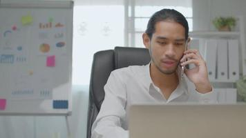 Asian Businessman Talk on Phone During Working on Laptop in Office video