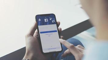 Chiang Mai, Tailandia, 23 de enero de 2021: persona que usa Facebook en un teléfono inteligente. foto