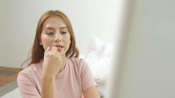 Feche o retrato de uma atraente garota asiática rouging os lábios. ela está segurando um batom rosa.