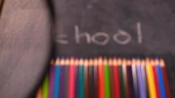palavra escolar e ferramentas educacionais lápis atrás de uma lupa