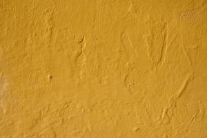 Yellow painted wall of an old house textured background photo