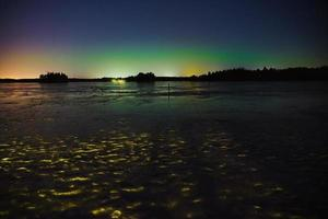Northern Lights over a frozen lake in Littoinen, Finland photo