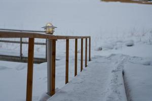Lantern on a snow-covered path with wooden railings in winter