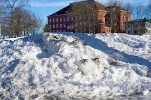 Dirty snow with an old brick house in the background photo