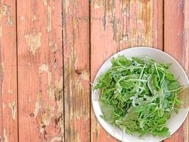 Arugula on a ceramic plate on a wooden table background photo