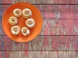Galletas en una placa naranja sobre un fondo de mesa de madera foto