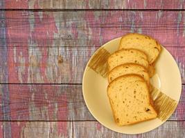 Rebanadas de pan en una placa de cerámica sobre un fondo de mesa de madera foto