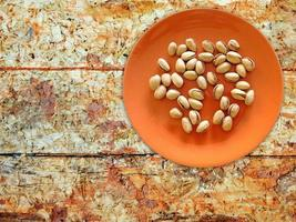 Pistachos en una placa de naranja sobre un fondo de mesa de madera foto