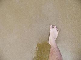 Male foot in the sand photo