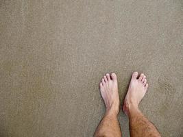 Feet of Asian male on the beach photo