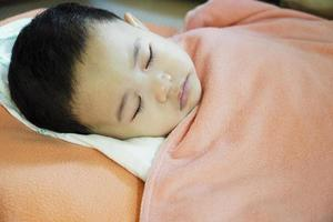 Close-up of a baby sleeping in bed photo