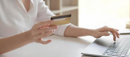 Hands holding a credit card and typing photo