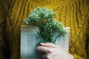 niña sosteniendo un libro y un ramo foto