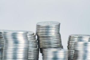 Pilas de monedas de plata sobre fondo blanco. foto