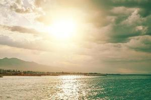 sol vespertino sobre un océano azul foto