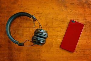 Vista superior de los auriculares y el teléfono inteligente en la mesa de madera foto