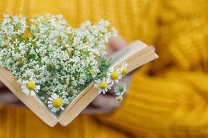 mujer sostiene libro con margaritas dentro foto