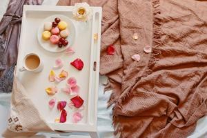 Romantic breakfast in bed with rose petals