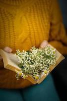 Chica en suéter de punto sostiene un libro con margaritas en el interior foto