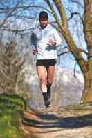 Man running on a mountain trail photo