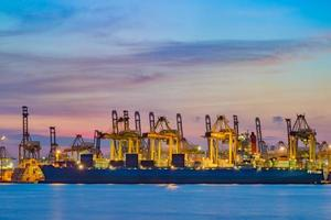 buque carguero cargando carga en el muelle de carga en el momento del crepúsculo. foto